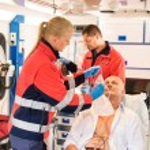 Paramedic putting oxygen mask on patient ambulance — Stock Photo