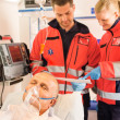 Paramedics reading EKG in ambulance patient help - ストック写真
