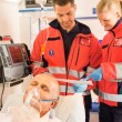 Paramedics reading EKG in ambulance patient help - Foto Stock