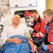 Paramedics checking patient pulse in emergency car — Stock Photo #13598086