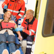 Paramedics help unconscious woman emergency aid - Stock Photo