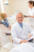 Mature dentist surgeon at office with patient — Stock Photo