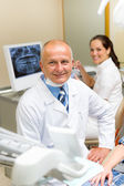 Mature dental surgeon in office with assistant — Stock Photo