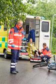 Paramédicos ajudando a ambulância de acidente de moto de mulher — Fotografia Stock
