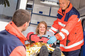 Paramedics helping woman in ambulance broken arm — Stock Photo
