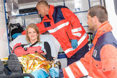 Woman with broken arm in ambulance paramedics — Zdjęcie stockowe