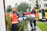 Paramedics with medical equipment ringing doorbell — Stock Photo