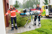 Paramedics carrying stretcher ambulance house call — Stok fotoğraf