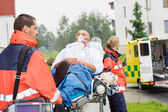 Paramedics with patient on stretcher ambulance aid — Stock Photo