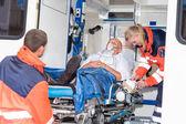 Paramédicos poniendo a paciente en ayuda coche ambulancia — Foto de Stock