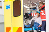 Paramedics checking IV drip patient in ambulance — Stock Photo