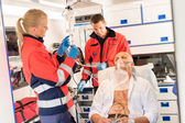 Paramedic putting oxygen mask on patient ambulance — Stock Photo