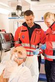 Paramedics reading EKG in ambulance patient help — Stock Photo