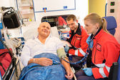 Paramedics checking patient pulse in emergency car — ストック写真
