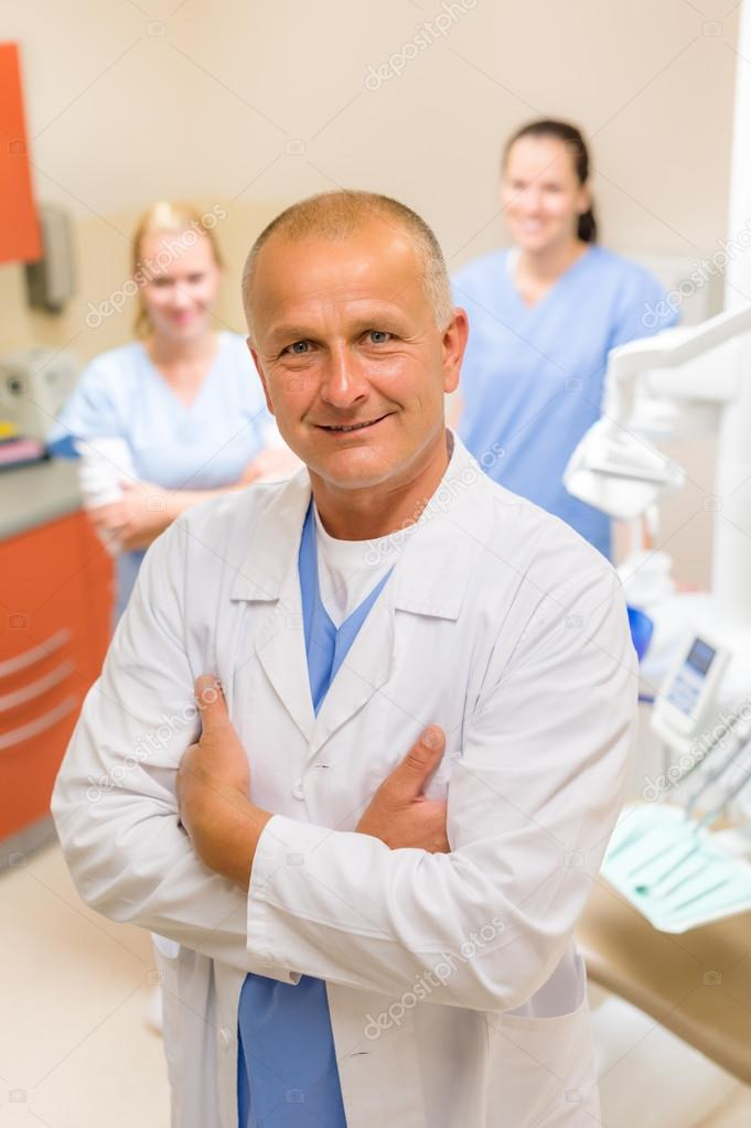 Portrait of mature dentist man with team in stomatology clinic — Stockfoto #13597928