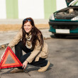 Woman putting warning triangle on the road - Stockfoto