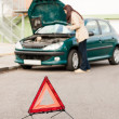 Woman trying to fix her broken car - Foto de Stock