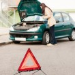 Woman trying to fix her broken car - Stock Photo
