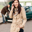 Woman on the phone repairman fixing car - Stock Photo