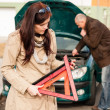 Woman worried about broken car warning sign — Stock Photo