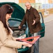 Woman holding triangle sign repairman fixing car — Stock Photo