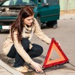 Woman putting triangle sign for car breakdown - Foto Stock