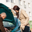 Man working on repairing a woman's car — Stock Photo #13603927