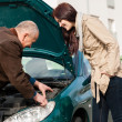 Stock Photo: Mworking on repairing woman's car