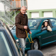 Man helping woman with her broken car - Stock Photo