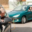 Man helping woman by pulling her car — Stock Photo