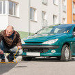 Mature man helping woman with her car - ストック写真