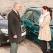 Man and woman talking after car crash - Stok fotoğraf