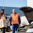 Woman shaking hands with mechanic car breakdown - Stock Photo