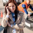 Stock Photo: Womtalking on cellphone after car breakdown