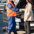 Woman greeting mechanic after her car breakdown - Stock Photo