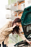 Woman looking under car hood on phone — Stock Photo