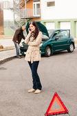 Upset woman on the phone car problem — Stock Photo