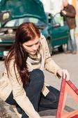 Araba arızası için üçgen işareti koyarak kadın — Stok fotoğraf
