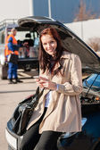 Woman dialing her phone after car breakdown — Stock Photo