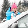 Woman cleaning car windshield of snow winter — Stock fotografie