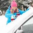 woman cleaning car windshield of snow winter — Stock Photo