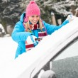 Woman cleaning car windshield of snow winter - Stok fotoğraf