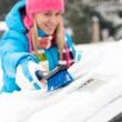 Woman wiping snow car window using brush — Stock fotografie