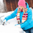 Woman cleaning snow car hood with scraper — ストック写真