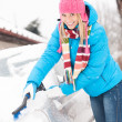 Woman cleaning car hood of snow brush — Stock Photo
