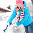 Woman cleaning car hood of snow brush — Stok fotoğraf #13814360