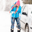 Woman having problems with car snow chains - Stock Photo
