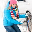 Woman putting chains on car winter tires - Zdjcie stockowe