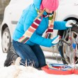 Woman putting chains on car winter tires — Stok fotoğraf #13814367