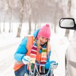 Woman with tire chains car snow breakdown - Stock Photo